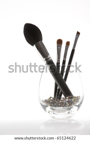a set of 4 make-up brushes, placed in a rounded transparent glass, with decorative beads. - stock photo
