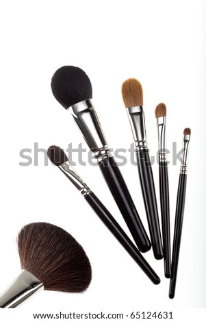a set of 6 make-up brushes, shot on white background. 5 of them are grouped together and counterbalanced by a larger powder brush on the left side of the picture. - stock photo