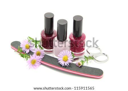 A set of manicure appliances: nail scissors, nail file and three shades of shiny nail polish isolated on white