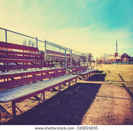 a set of old wooden bleachers for cheering on a sporting event at a local high school toned with a retro vintage instagram filter app or action effect - stock photo