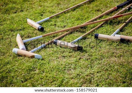 A set of Polo Rackets lying on the grass. - stock photo