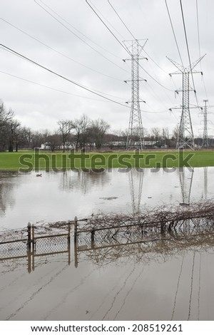 A set of power lines span the flood that engulfed the area with flood damage. - stock photo