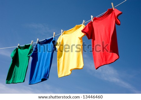 a set of primary colored T-shirts hanging on a clothesline on a beautiful, sunny day, add text or graphic to shirts or copy space - stock photo