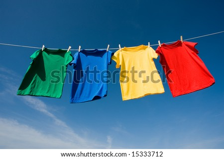 a set of primary colored T-shirts hanging on a clothesline on a beautiful, sunny day, add text or graphic to shirts or copy space