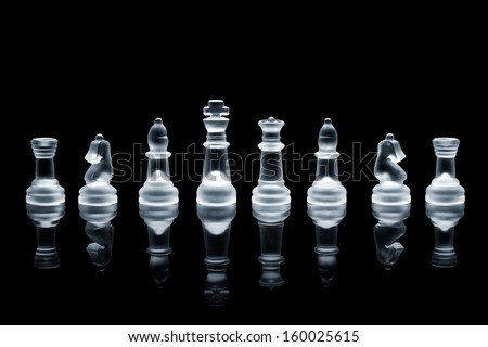 A set of semi transparent chess pieces on reflective surface. - stock photo