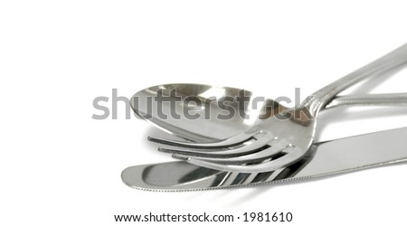 A set of stainless steel knife, fork and a spoon on white background with copyspace. - stock photo