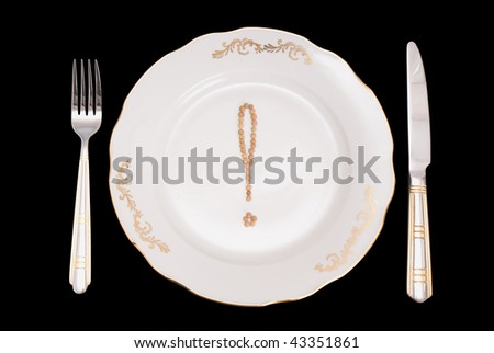 A set of tablewares on a black background. On a plate the sign on a exclamation mark from lentil is laid out. - stock photo