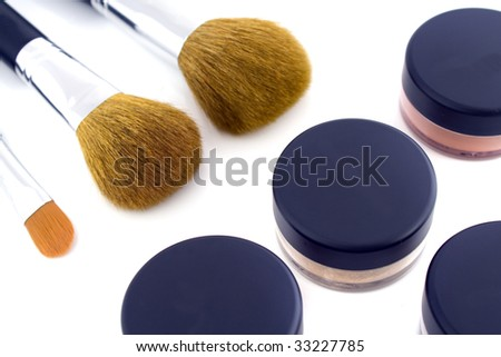 A set of three make-up brushes and four jars with mineral powder foundation. Isolated on white background.