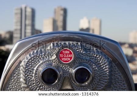 A set of tourist binoculars looks towards a dense part of San Francisco. - stock photo