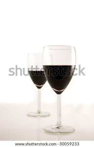 A set of two red wine glasses for a romantic encounter - stock photo