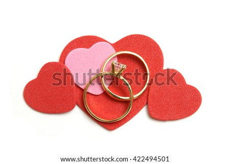 A set of wedding rings with some decorative heart shapes to compliament the theme of love. - stock photo