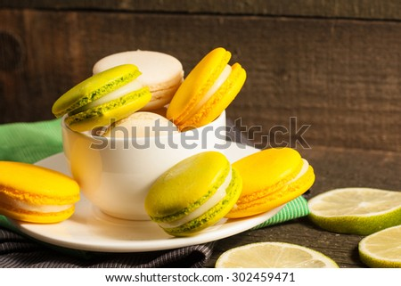 A set of white coffee cup with yellow and green macarons on a rustic wooden background