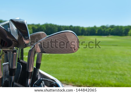 A set up new golf clubs on a black golf course - stock photo