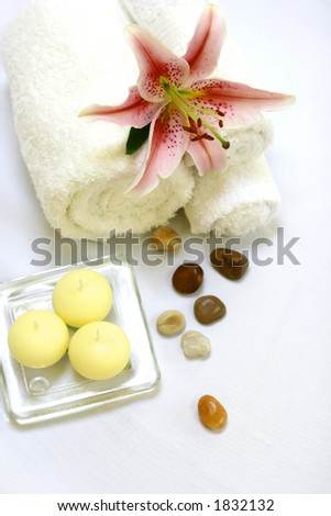 A setting for a spa consisting of white towels, a candle, therapy stones and a lily on white - stock photo