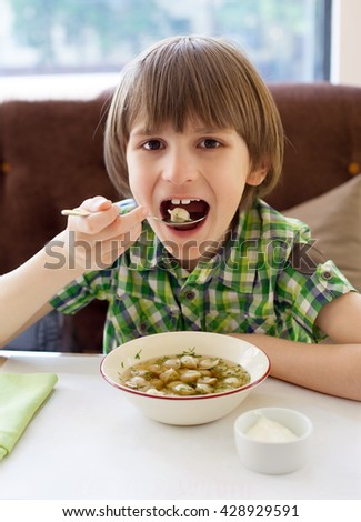 A seven years kid is eating Russian ravioli in cafe - stock photo