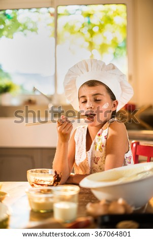 A seven years old girl with chef hat is holding a wooden spoon full of chocolate. She is closing her eyes, sitting at a wooden table full of ingredients. She looks delighted with flour on her face - stock photo