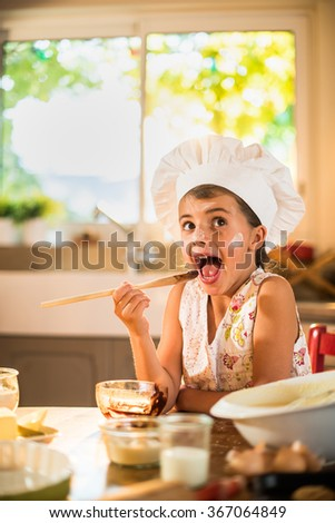 A seven years old girl with chef hat is licking a wooden spoon full of chocolate. She is looking at camera, sitting at a wooden table full of ingredients. She looks delighted. - stock photo
