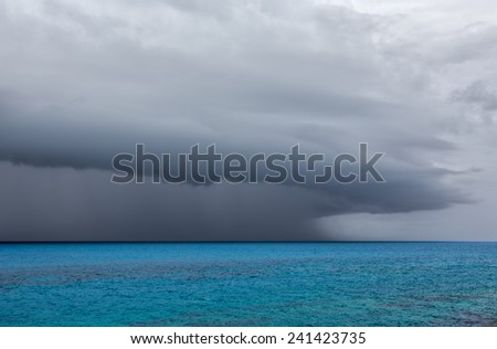 A severe thunderstorm over the ocean off the coast of Bermuda. The anvil shaped cumulonimbus incus clouds are seen with rain falling. - stock photo