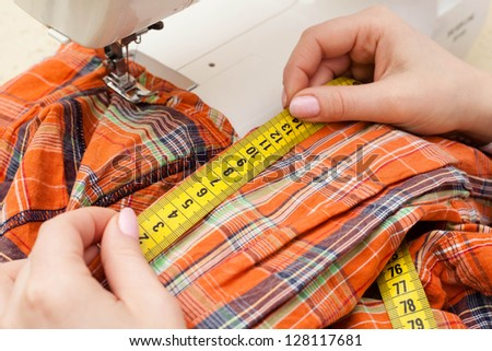 A sewer measuring a garment. - stock photo