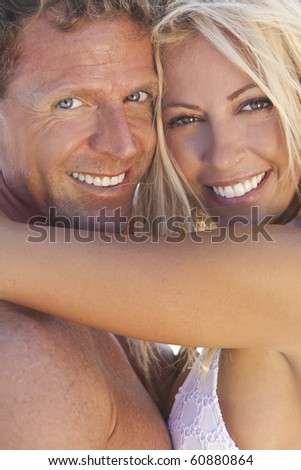 A sexy and attractive man and woman couple smiling and happy in the sunshine at the beach