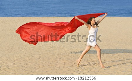 A sexy and beautiful young brunette woman running along a golden beach with a length of red material and a deep blue sea behind her.