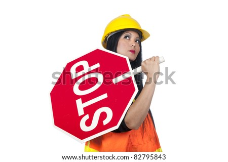 A sexy Asian woman in construction clothing holds a stop sign. - stock photo