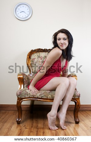 A sexy full body shot of a young woman sitting on a old chair on laminated floor with a red dress. - stock photo