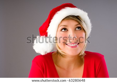 A sexy girl in Santa Hat wonder what she will get for christmas - stock photo