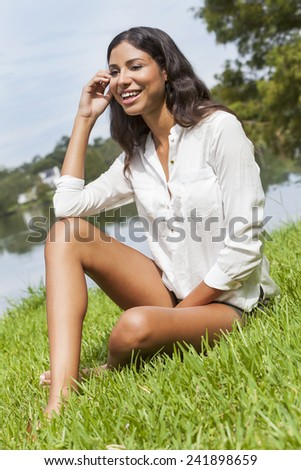A sexy happy young Latina Hispanic brunette woman or girl wearing shorts laughing sitting on the grass by a lake on a sunny summer day - stock photo