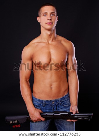 A sexy male is holding a big black gun - stock photo