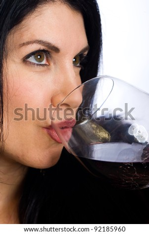 A sexy middle aged woman with black hair drinking a glass of red wine.