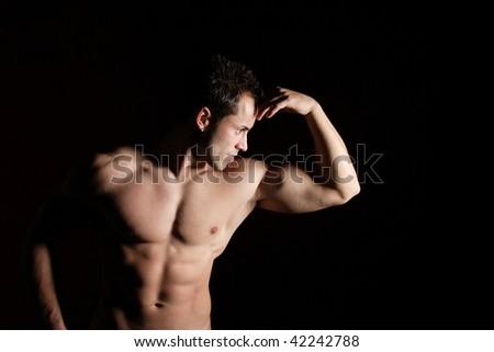 A Sexy muscular man on dark background - stock photo