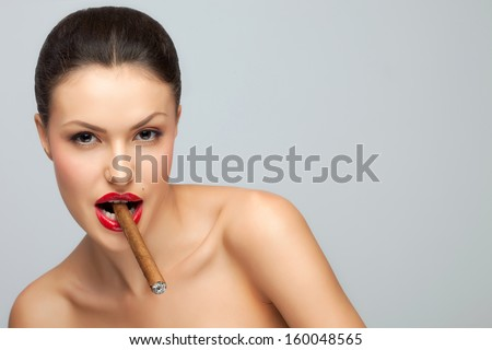 A sexy nude lady holding cigar in her mouth. - stock photo