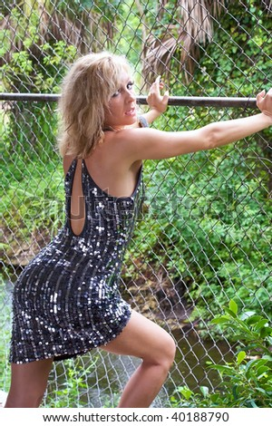 A sexy shapely lady is looking over her shoulder at the viewer while leaning on a chain link fence with her knee bent - stock photo