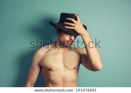 A sexy shirtless young man is wearing a cowboy hat - stock photo
