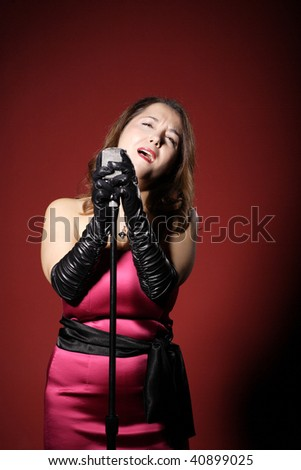 A sexy singer with a vintage microphone on red background