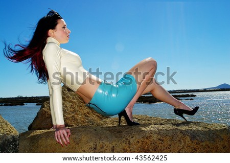 A sexy woman wearing white and blue latex standing against a bright blue sky - stock photo