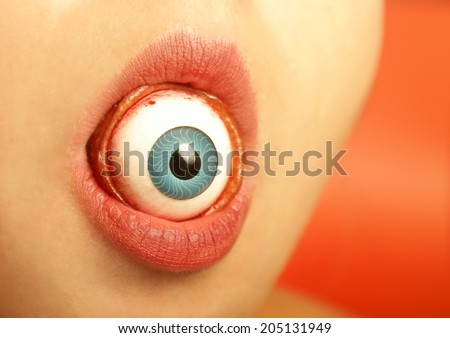 A sexy womans lips swallows an eyeball. - stock photo