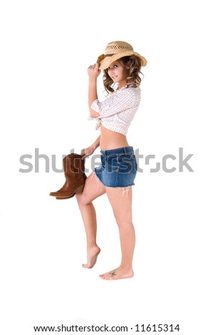 A sexy young barefooted cowgirl with pigtails smiling and holding her boots - stock photo
