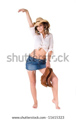 A sexy young barefooted cowgirl with pigtails smiling and holding her boots in one hand while dancing - stock photo