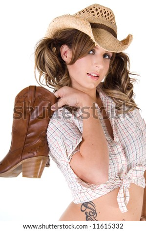 A sexy young barefooted cowgirl with pigtails smiling and holding her boots over her right shoulder - stock photo