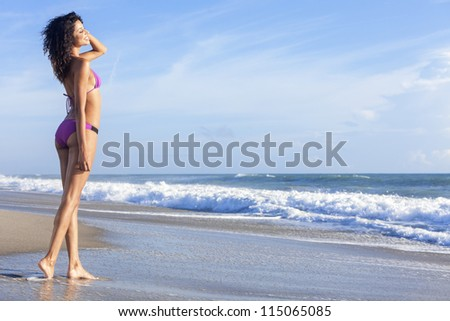 A sexy young brunette woman or girl wearing a purple bikini on a deserted tropical beach with a blue sky - stock photo