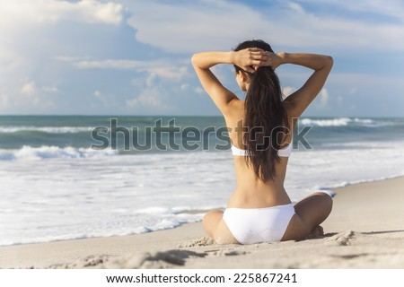A sexy young brunette woman or girl wearing a white bikini sitting on a deserted tropical beach with a blue sky  - stock photo