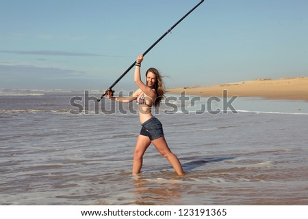 a sexy young lady in bikini is casting her line trying to catch a fish in the ocean.