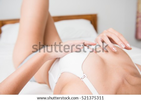 A sexy young woman lying on her bed in lingerie