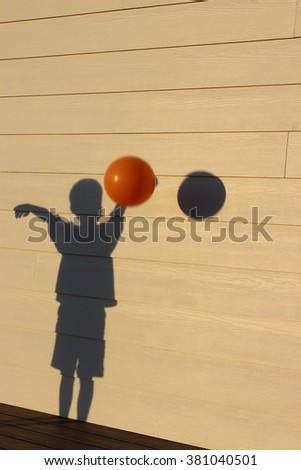 A Shadow of a Boy Playing Basketball with the Real Ball