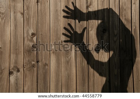 a shadow or silhouette of a man against a wooden fence - stock photo