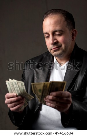 A shady looking man counting a handful of one hundred dollar bills. Shallow depth of field with focus on the face.