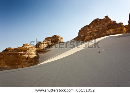 A shaft of sunlight filters through the rocks creating a streak across the white desert sands with the mountain rocks behind - stock photo