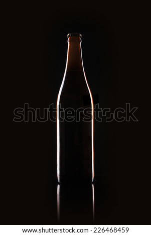 A shaking beer bottle at reflective bottom with bobble isolated black - stock photo